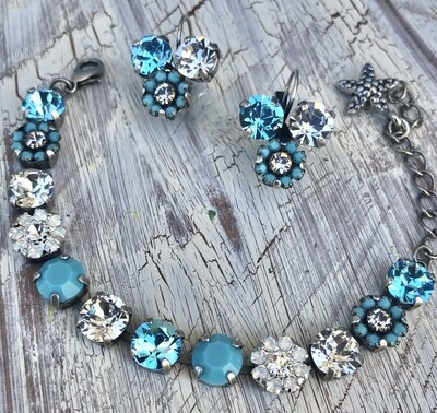 "The name of this bracelet is called, ""A Touch Of Turquoise "".  This bracelet has opal and turquoise flowered elements with Swarovski stones. The setting is antique silver."