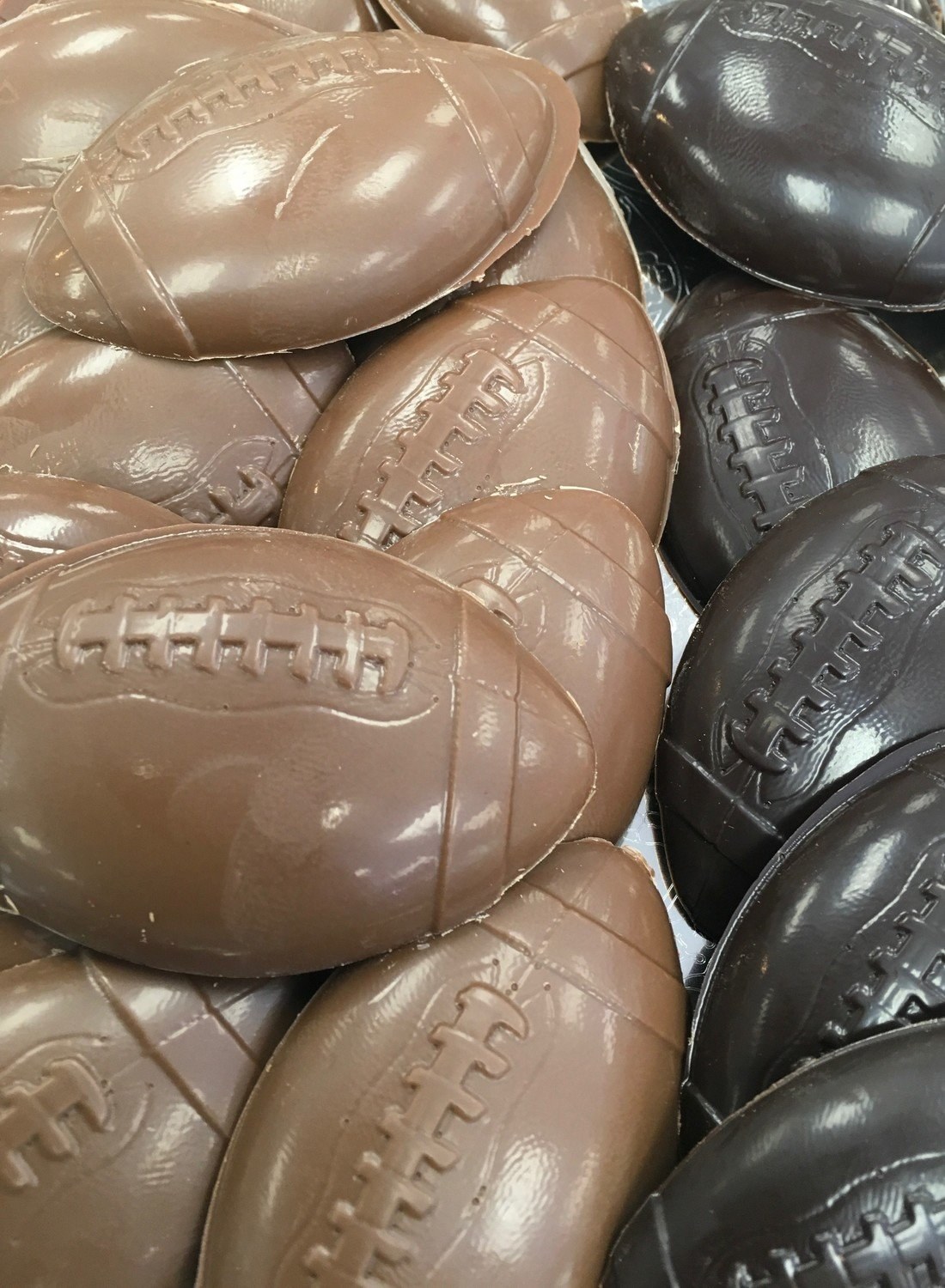 """Solid Chocolate Footballs.  3""""x2"""" approx.  Peanut and Gluten Free.  20 to a Lb."""