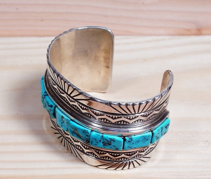 The front view of the vintage cobblestone cuff showing the wide band with intricate stamp work and rows of turquoise stones in the middle